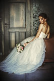 La novia hermosa se sienta en una silla de cuero en un cuarto oscuro Fotos de archivo