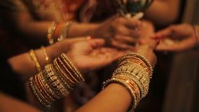 La novia hindú y sus padres llevan a cabo las manos en pulseras detrás de ramas de árbol metrajes