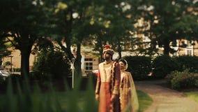 La novia india asombrosa en rojo y traje de la boda del oro se coloca detrás de un novio en el jardín almacen de video