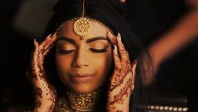 La novia india de fascinación se sostiene los fingeres delicados detrás de sus templos mientras que las mujeres consiguen le el p almacen de metraje de vídeo