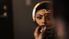 La novia india hermosa sostiene un espejo redondo mientras que la mujer pinta sus labios almacen de metraje de vídeo