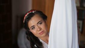 La novia joven admira su vestido de boda blanco asombroso metrajes