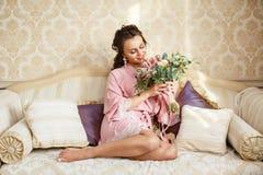 La novia joven hermosa con los pelos oscuros se sienta en un sofá en un dormitorio Mañana del ` s de la novia Fotos de archivo libres de regalías