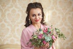 La novia joven hermosa con los pelos oscuros se sienta en un sofá en un dormitorio Mañana del ` s de la novia Fotos de archivo