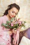 La novia joven hermosa con los pelos oscuros se sienta en un sofá en un dormitorio Mañana del ` s de la novia Imagen de archivo libre de regalías