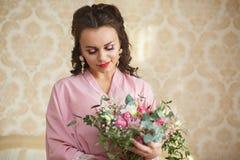 La novia joven hermosa con los pelos oscuros se sienta en un sofá en un dormitorio Mañana del ` s de la novia Imagen de archivo