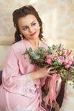 La novia joven hermosa con los pelos oscuros se sienta en un sofá en un dormitorio Mañana del ` s de la novia Foto de archivo libre de regalías