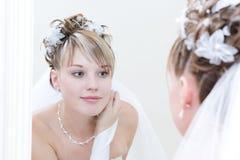La novia joven mira en un espejo grande Fotografía de archivo