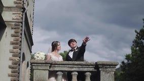 La novia lleva al novio en el castillo El caminar feliz de los recienes casados almacen de metraje de vídeo