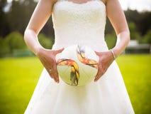 La novia lleva a cabo el fútbol en sus manos fotografía de archivo libre de regalías