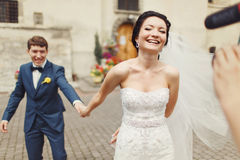 La novia lleva a cabo la mano del novio que camina con él al cameraman Imagen de archivo libre de regalías