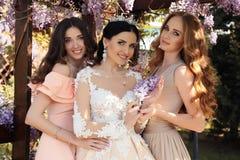 La novia magnífica en vestido de boda y la corona que presenta en verano del flor cultivan un huerto Fotografía de archivo libre de regalías