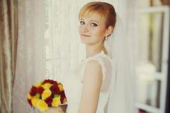 La novia mira la situación misteriosa con un ramo detrás de una ventana imágenes de archivo libres de regalías