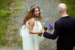 La novia mira sobre su hombro que se coloca en el parque imagen de archivo libre de regalías