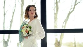 La novia morena hermosa sostiene un ramo de la flor cerca del window-2 Tiara hermosa en el pelo, maquillaje profesional almacen de metraje de vídeo