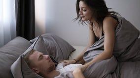 La novia morena joven está despertando su novio o husbund por la mañana Divirtiéndose junto en la cama gris almacen de video