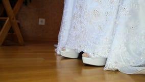 La novia muestra a tacón alto los zapatos blancos fuera del primer del vestido de boda almacen de metraje de vídeo