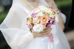 La novia que lleva a cabo la boda hermosa florece el ramo Imagen de archivo libre de regalías