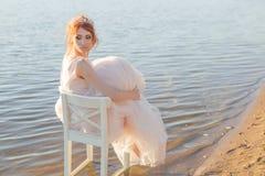 La novia que se sienta en una silla en el vestido observado agua y mira la puesta del sol Foto de archivo libre de regalías
