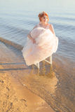 La novia que se sienta en una silla en el vestido observado agua y mira la puesta del sol Fotos de archivo libres de regalías