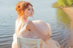 La novia que se sienta en una silla en el vestido observado agua y mira la puesta del sol Fotos de archivo
