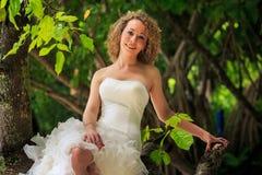 la novia rubia en vestido mullido se sienta en soportes del novio del tronco cerca Fotos de archivo