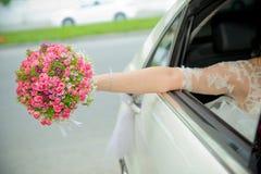 La novia sacó el ramo rosado de la flor del coche la muchacha de la novia va a casarse los coches y a agitar con un ramo de él T imagenes de archivo