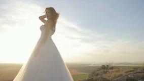 La novia se está colocando al lado del novio en las montañas oscila en la puesta del sol almacen de video