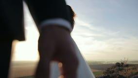 La novia se está colocando al lado del novio en las montañas oscila en la puesta del sol metrajes