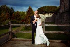 La novia sonríe abrazando a un novio en un puente de madera viejo fotografía de archivo