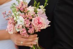 la novia sostiene el ramo que se casa en sus manos, el novio la abraza en frente imagen de archivo libre de regalías