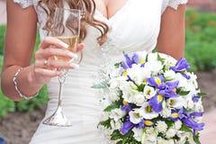 la novia sostiene el vidrio disponible de champán y de weddin Fotografía de archivo