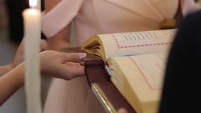 La novia sostiene la Sagrada Biblia en iglesia en ceremonia de boda almacen de video