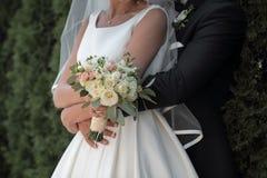 La novia sostiene un ramo de la boda en manos Foto de archivo libre de regalías