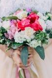 La novia sostiene un ramo que se casa de diversas flores en sus manos Cierre para arriba foto de archivo
