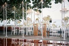 La novia y el asiento del novio de detrás en la preparación con las rosas blancas, decoración blanca de la tabla de cena de la re Fotos de archivo
