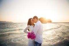 la novia y el novio abrazan en el escupitajo en la salida del sol Fotografía de archivo