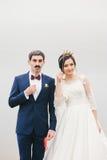 La novia y el novio atados a la cara empapelan el bigote, corona Imágenes de archivo libres de regalías