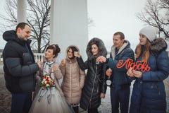 La novia y el novio caminan en el parque con los amigos en un día de invierno Imagen de archivo libre de regalías