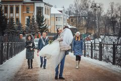La novia y el novio caminan en el parque con los amigos en un día de invierno Imágenes de archivo libres de regalías