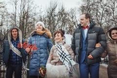 La novia y el novio caminan en el parque con los amigos en un día de invierno Fotos de archivo libres de regalías