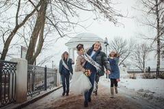 La novia y el novio caminan en el parque con los amigos en un día de invierno Imagen de archivo