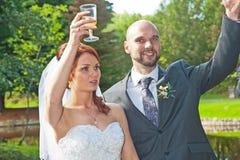 La novia y el novio celebran Foto de archivo libre de regalías