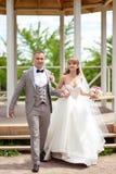 La novia y el novio con un ramo van en el fondo de un cenador blanco foto de archivo