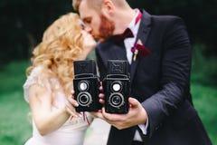 La novia y el novio con una cámara vieja a disposición fotografía de archivo libre de regalías