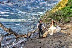 La novia y el novio consiguen casados en una playa en Costa Rica tropical imagenes de archivo