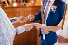 La novia y el novio consiguen un anillo del sacerdote Fotografía de archivo