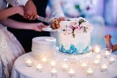 La novia y el novio cortaron el cierre del pastel de bodas imágenes de archivo libres de regalías