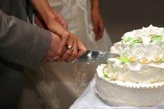 La novia y el novio cortaron el primer del pastel de bodas Foto de archivo