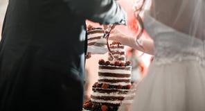 La novia y el novio cortaron la torta de boda Con gradas multi redondo con la esponja, la crema, el atasco y bayas en una base ci Imagen de archivo